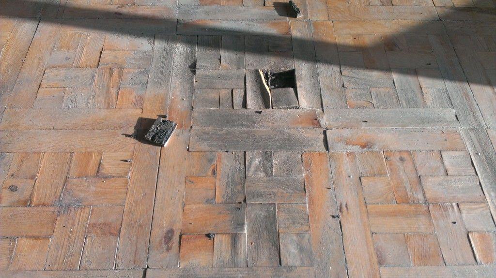 Parquet hidráulico castaño con brea en mal estado por humedad y sol